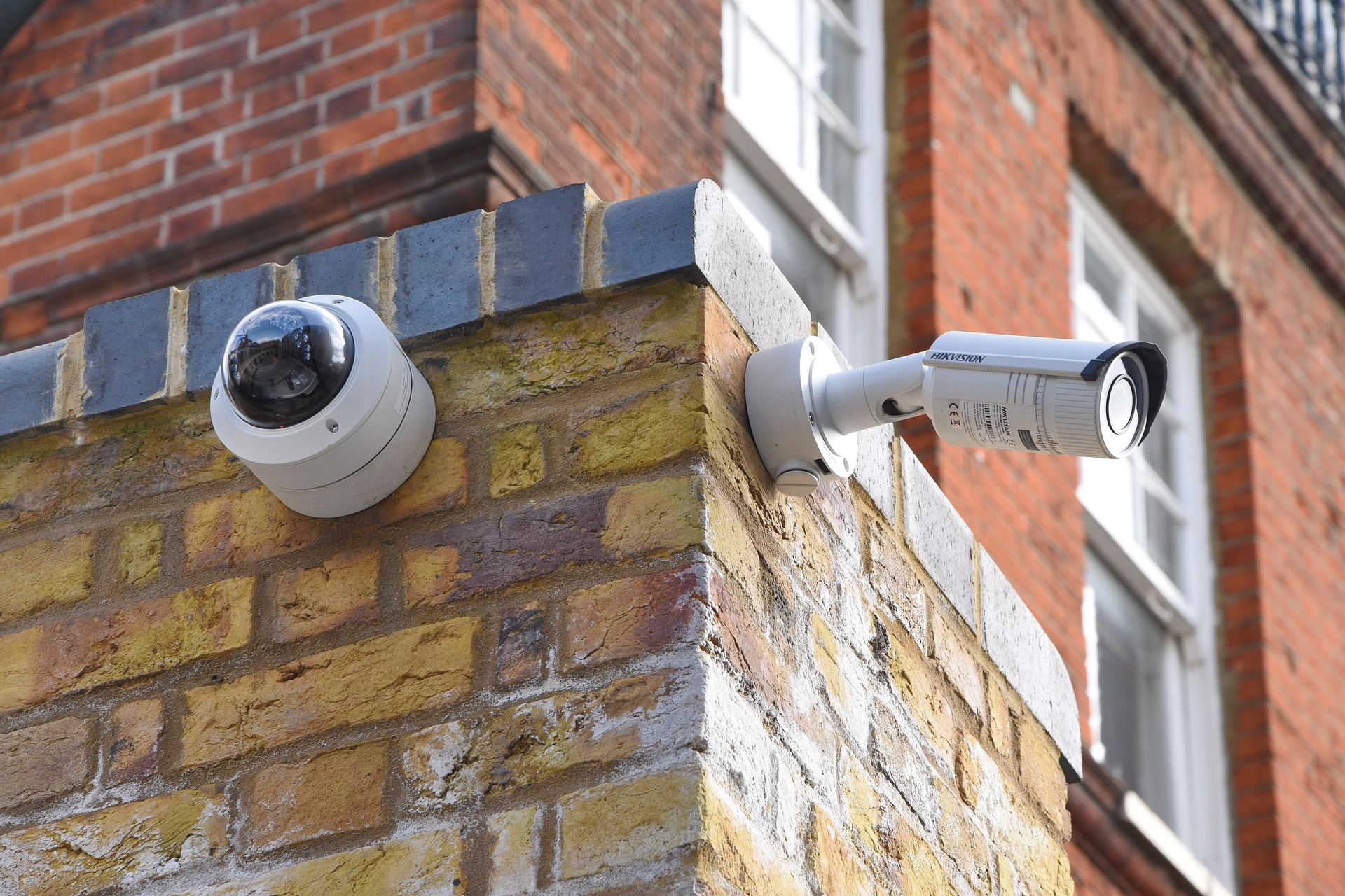 two security cameras mounted on brick corner